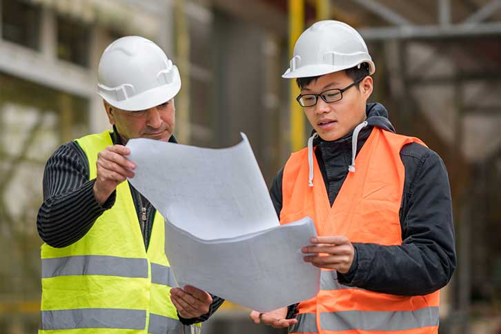 Two construction workers looking at building blueprints