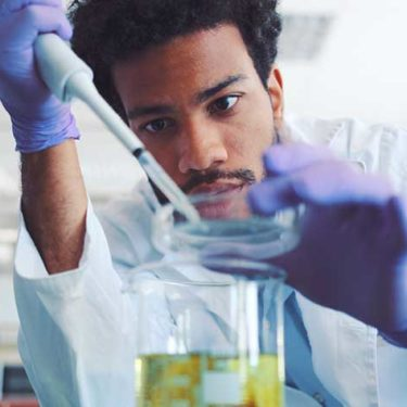 man working with petri dish in lab coat and gloves